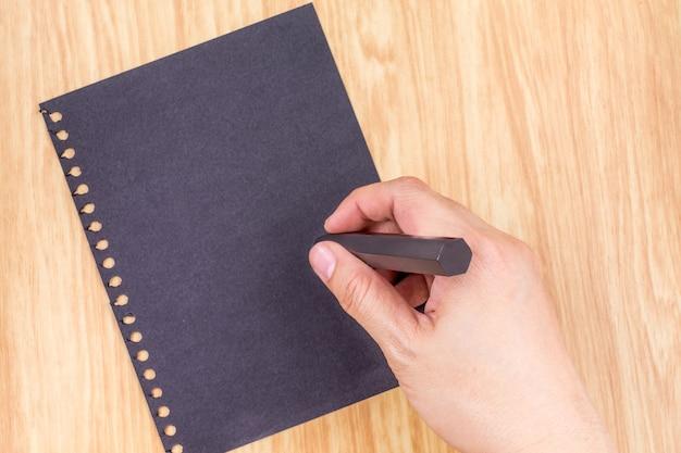 Mão escrevendo no paperl preto no tampo da mesa de madeira