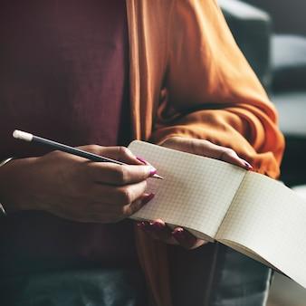 Mão escrevendo nota em um caderno