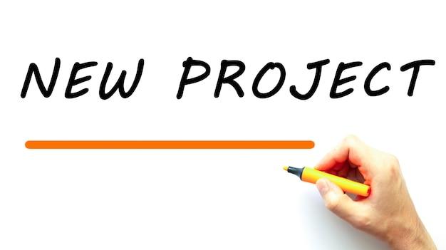 Mão escrevendo novo projeto com marcador. isolado no fundo branco. conceito de negócios.