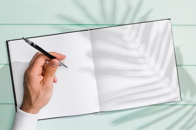 Mão escrevendo num caderno em branco e sombra de folhas