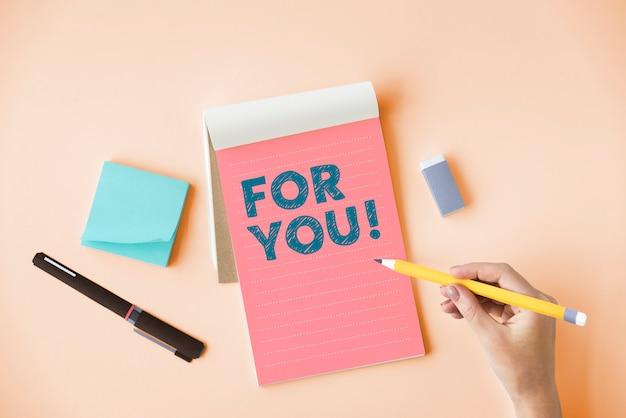 Mão escrevendo para você em um bloco de notas