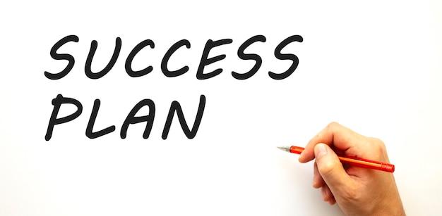 Mão escrevendo plano de sucesso com caneta isolada no fundo branco