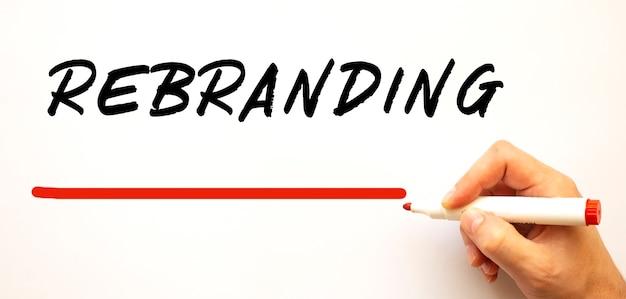 Mão escrevendo rebranding com marcador vermelho. isolado na superfície branca.