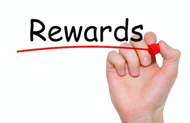 Mão escrevendo recompensas com marcador vermelho no quadro transparente.