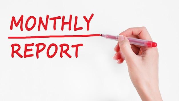 Mão escrevendo relatório mensal de inscrição com marcador, conceito, imagem de estoque