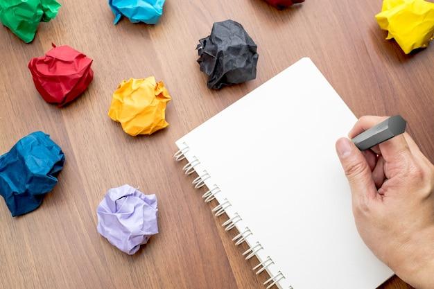 Mão, escrita, em, livro branco em branco aberto, pasta, livro branco, e, lápis, com, grupo, de, coloridos, papel
