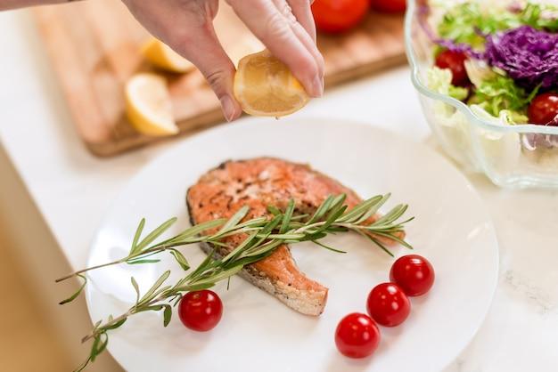 Mão esmagando limão no prato de peixe
