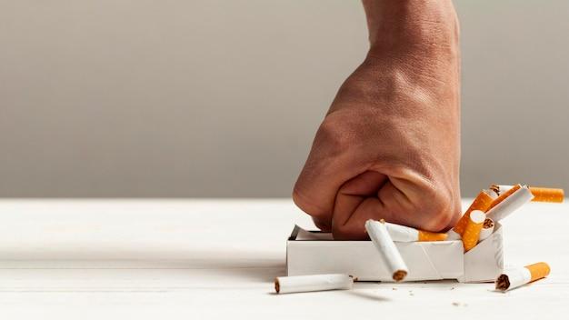 Mão esmagando maço de cigarros