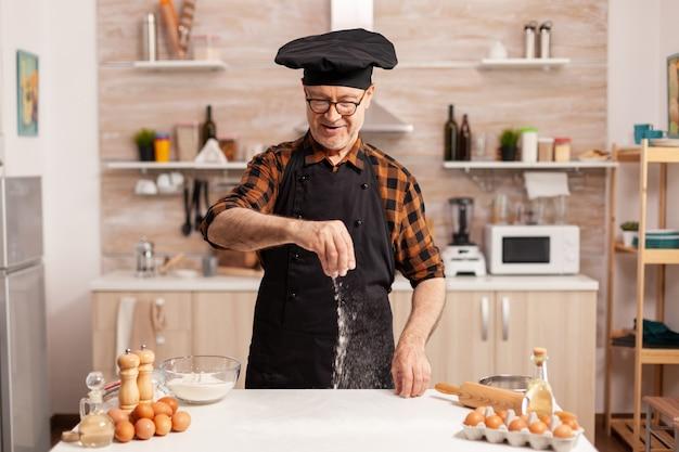 Mão espalhando farinha de trigo na mesa da cozinha de madeira para pizza caseira. chef sênior aposentado com bonete e avental, em uniforme de cozinha, polvilhando ingredientes peneirados com a mão.