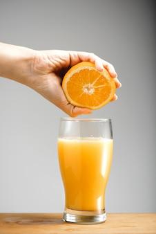 Mão espremendo suco de laranja em vidro