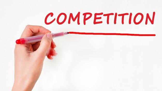 Mão esquerda escrevendo competição de inscrição com marcador de cor vermelha, conceito, imagem conservada em estoque
