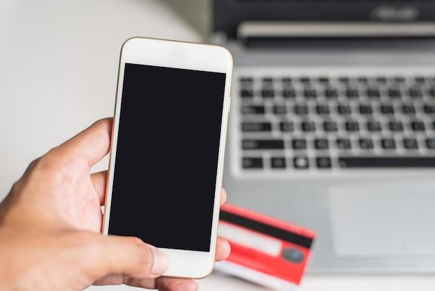 Mão esquerda, usando, smartphone, ligado, borrão blackground, com, laptop, e, cartão crédito