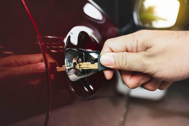 Mão está destrancando a porta do carro com a chave na garagem fechada