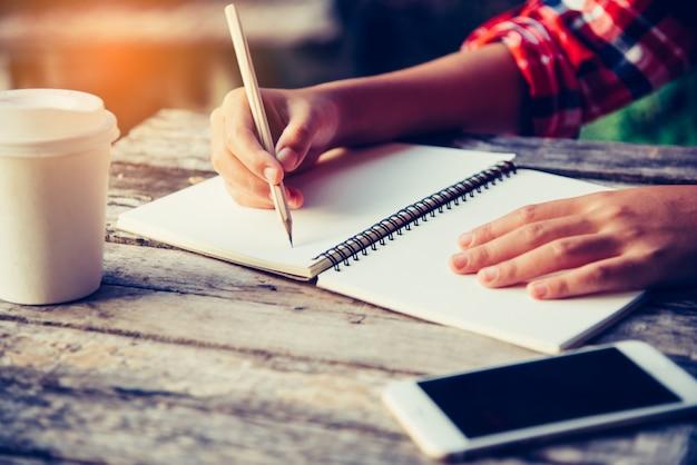 Mão está escrevendo no caderno com um lápis e uma xícara de café