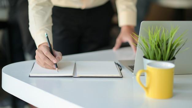 Mão está escrevendo uma nota em um notebook com uma caneca de café e um laptop em cima da mesa.