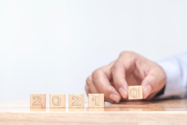 Mão está mudando um cubo de madeira muda simbolicamente de 2020 a 2021