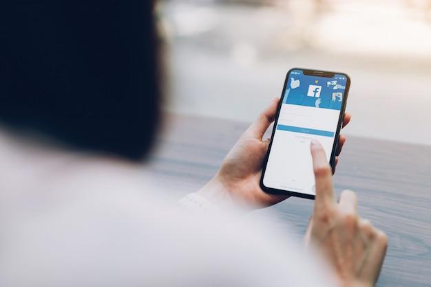Mão está pressionando a tela do facebook no apple iphone x, mídias sociais.