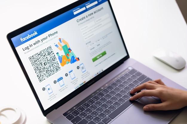 Mão está pressionando a tela do facebook no laptop