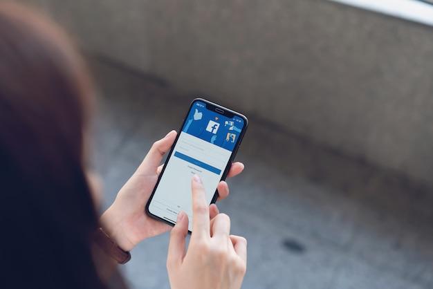 Mão está pressionando a tela do facebook no telefone inteligente da apple, mídias sociais estão usando para compartilhamento de informações e redes.