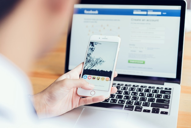 Mão está pressionando a tela do facebook no telefone.