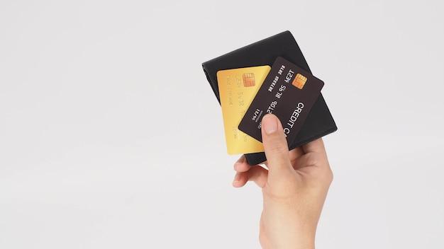 Mão está segura cartão de crédito cor preta e dourada com carteira preta isolada no fundo branco.