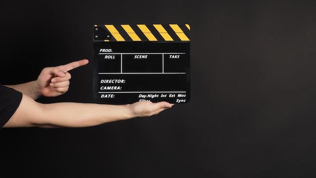 Mão está segurando e apontando para claquete amarelo e preto ou filme ardósia uso na produção de vídeo e na indústria do cinema em fundo preto.
