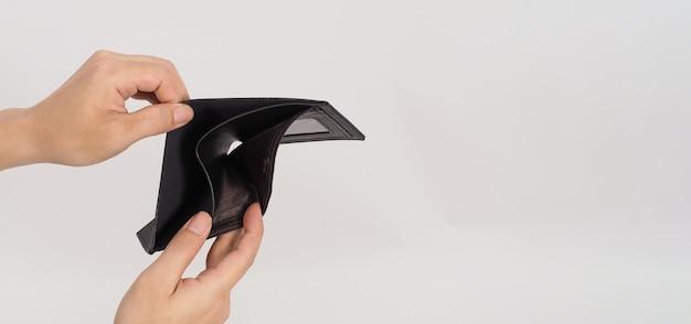 Mão está segurando e carteira vazia preta aberta isolada no fundo branco.