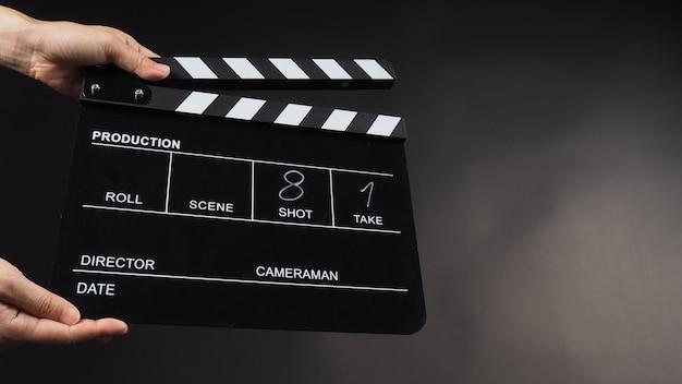 Mão está segurando gonorréia preta ou uso de ardósia de filme na produção de vídeo, filme, cinema, indústria do cinema em fundo preto. tem escrever em número.