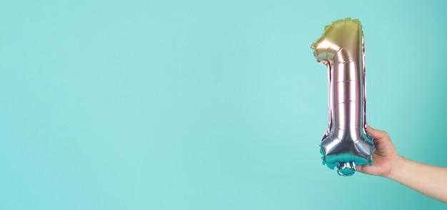 Mão está segurando o balão número 1 em fundo azul menta ou tiffany.