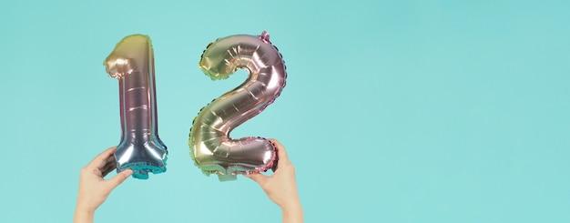 Mão está segurando o balão número 12 ou 12 em fundo azul menta ou tiffany.