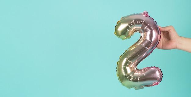 Mão está segurando o balão número 2 em fundo azul menta ou tiffany.