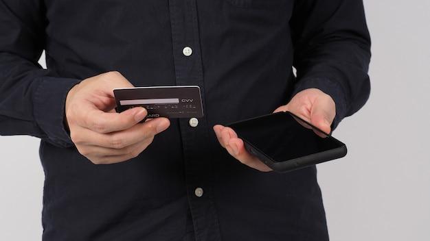 Mão está segurando o celular e o cartão de crédito preto sobre fundo branco.
