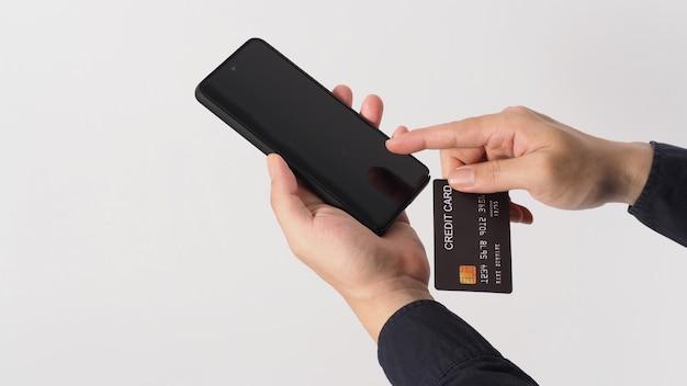 Mão está segurando o telefone celular e o cartão de crédito preto sobre fundo branco. mão do homem asiático.