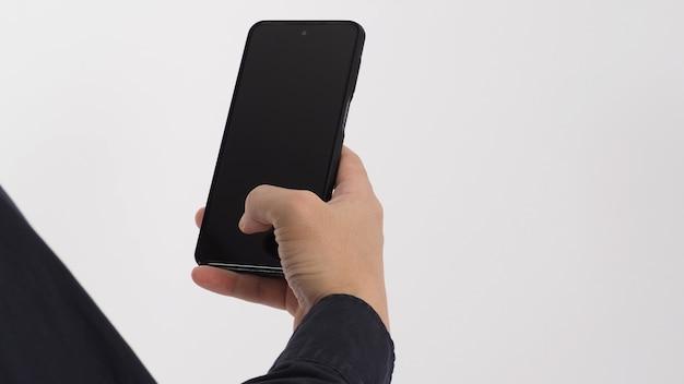 Mão está segurando o telefone móvel isolado no fundo branco. Foto Premium