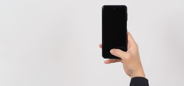 Mão está segurando o telefone móvel isolado no fundo branco.