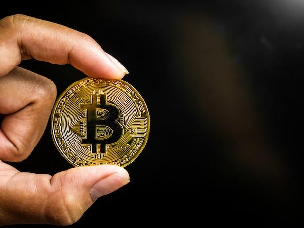 Mão está segurando ouro bitcoin.
