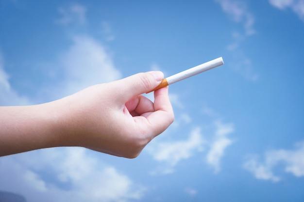 Mão está segurando um cigarro sobre fundo azul, não fumar. parando do conceito de vício.