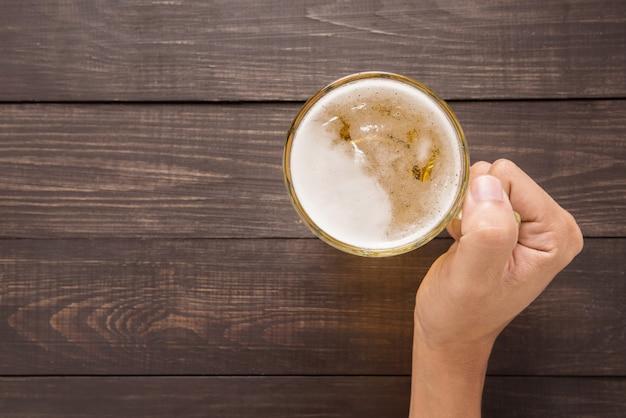 Mão está segurando um copo de cerveja no pub