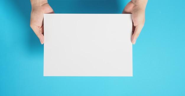 Mão está segurando um papel cartão em branco sobre fundo azul.