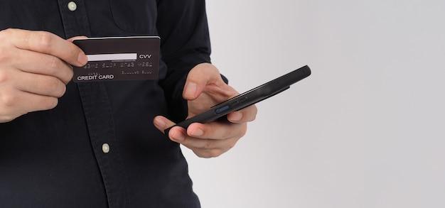 Mão está segurando um telefone inteligente e um cartão de crédito preto sobre fundo branco. olympus digital camera