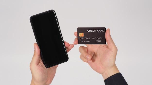 Mão está segurando um telefone inteligente e um cartão de crédito preto sobre fundo branco.
