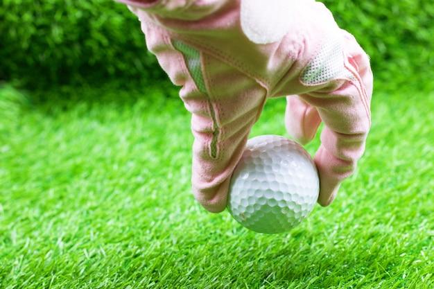 Mão está segurando uma bola de golfe na grama verde