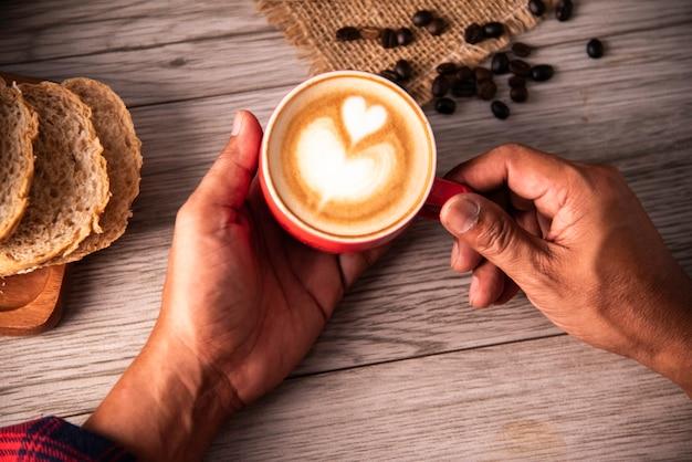 Mão está segurando uma xícara de café vermelha. conceito ainda vida