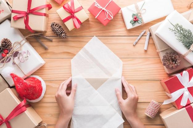 Mão estão embrulhando presentes da decoração de feliz natal e feliz ano novo para a celebração