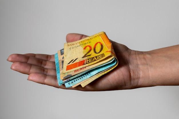 Mão estendida com notas de dinheiro brasileiras