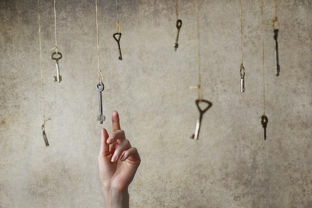 Mão esticando-se para pegar uma das muitas chaves vintage penduradas em fios