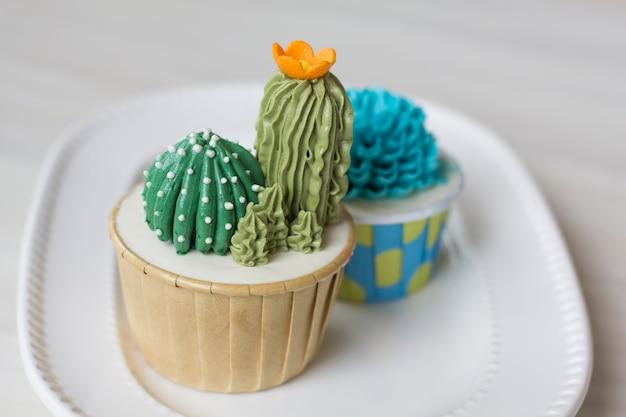 Mão faça cupcakes de cacto com buttercream branco