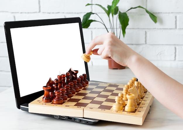 Mão faz uma jogada no jogo de xadrez no tabuleiro de vídeo no chat online.