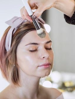 Mão fazendo maquiagem no cliente