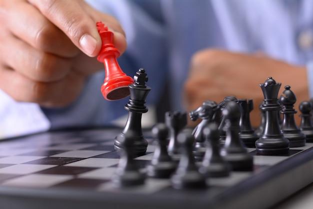 Mão fazendo movimento em um jogo de xadrez, movendo o peão um campo para a frente.